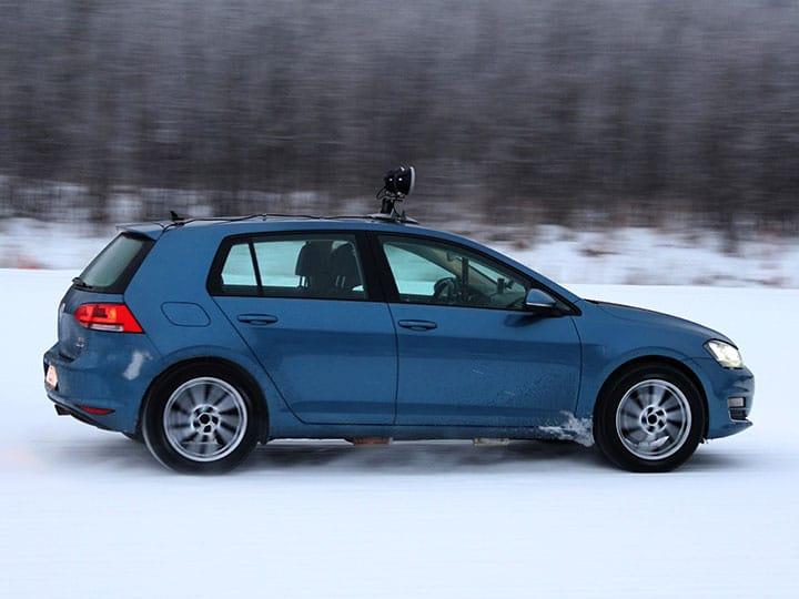 Ein VW Golf fährt eine Kurve auf verschneiter Fahrbahn für den Test der Winterreifen 2021 von ADAC und TCS
